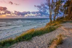 Härlig solnedgång på Östersjön med färgrik molnig himmel som är guld- Arkivbilder