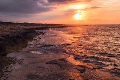 Härlig solnedgång på den steniga kustlinjen Royaltyfria Bilder