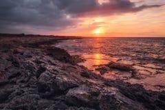 Härlig solnedgång på den steniga kustlinjen Fotografering för Bildbyråer