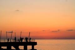 härlig solnedgång på havet, fishman Royaltyfri Foto