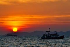 Härlig solnedgång på havet och fiskebåten Arkivfoton