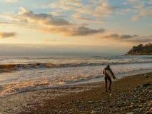 Härlig solnedgång på konturn för havskust av en surfare som bort går längs kustlinjen royaltyfria foton