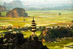 Härlig solnedgånglandskapsynvinkel med den vita stupaen uppifrån av M.U.A.-grottaberget, Ninh Binh, Tam Coc, Vietnam arkivbild