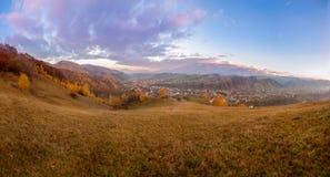 Härlig solnedgångpanorama med skogar, berg och byn Royaltyfri Foto