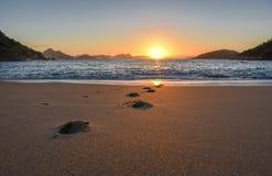 Härlig soluppgång, den sol- banan på vatten och fotspår på den öde praiaen Vermelha sätter på land royaltyfria bilder