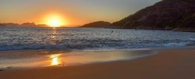 Härlig soluppgång, den sol- banan på vatten och sand på den öde praiaen Vermelha sätter på land royaltyfria foton