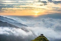 Härlig soluppgång med molnet på berget Arkivbild