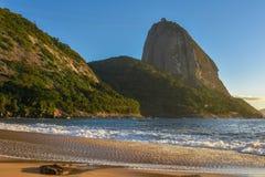 Härlig soluppgång på den öde PraiaVermelha stranden med den ljusa solen som exponerar det Sugarloaf berget Arkivbild