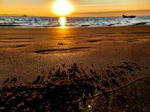 Härlig soluppgång på ett Pebble Beach med sand och fotsteg fotografering för bildbyråer