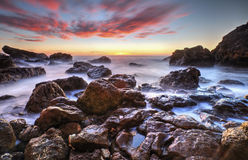 Härlig soluppgång på stenig kust Arkivfoto