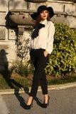 Härlig som en lady kvinna som bär den eleganta blusen, flåsanden och hatten Royaltyfri Fotografi