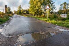 härlig sommar för bygddagväg Brunst med pölar för vägmärketon för vinkel blå sikt wide arkivfoto