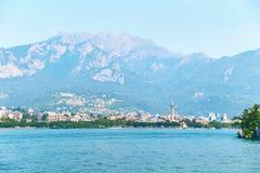 Härlig sommarsikt av staden av Lecco i Italien på kusten av sjön Como med tornet för synlig klocka av kyrkan av Royaltyfri Bild