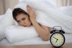 Härlig sova kvinna som ligger i säng och försöker att vakna upp med ringklockan Flicka som har problem med att få upp tidigt Royaltyfri Fotografi