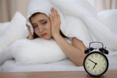 Härlig sova kvinna som ligger i säng och försöker att vakna upp med ringklockan Flicka som har problem med att få upp tidigt Fotografering för Bildbyråer