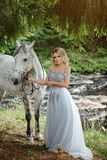 Härlig spenslig blond flicka i klänning som kramar en grå häst, outd royaltyfria bilder