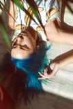 Härlig spenslig flicka i underbyxor och en T-tröja med blått hår som poserar på golvet bredvid en blomma i en kruka Arkivbild