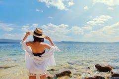 Härlig spenslig flicka som kopplar av på den steniga stranden av en stor sjö royaltyfri fotografi