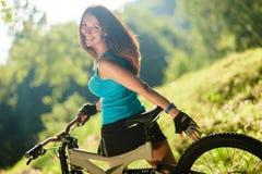 Härlig sportflicka med den utomhus- cykeln Fotografering för Bildbyråer