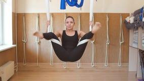 Härlig sportig kvinna med att räcka för höftöppning som är uppochnervänt på hängmattan lager videofilmer