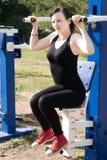 Härlig sportig kvinna som gör sportar på gatan Flickan på trampkvarnen royaltyfri foto