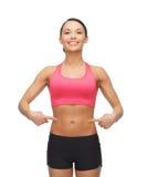 Härlig sportig kvinna som pekar på hennes sex packe Arkivbild