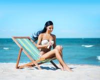 Härlig, sportig och sexig kvinna för barn som, tillfogar solkräm Fotografering för Bildbyråer