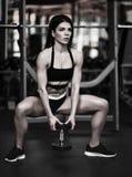 Härlig sportig sexig kvinna som gör satt genomkörare i idrottshall arkivbilder