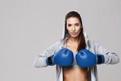 Härlig sportive flicka som ser kameran som bär handskar för blå ask som utbildar över vit bakgrund Arkivfoto