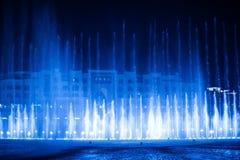 Härlig springbrunn på natten som är upplyst med blått ljus Arkivbild