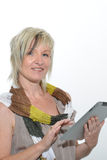 Härlig stående övre blond hög kvinna som arbetar med minnestavlaPC Royaltyfria Foton