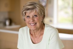 Härlig stående av den mogna kvinnan för nätt och söt pensionär i mellersta ålder omkring 70 gamla år le lycklig och vänlig hemmas Arkivbild
