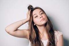 Härlig stående av den unga brunettkvinnan med långt hår på vit bakgrund fotografering för bildbyråer