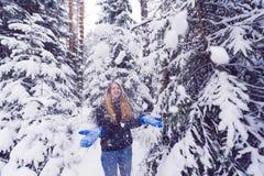 Härlig stående av en flicka i vinterskog som ler kvinnan som spelar i snö Royaltyfria Bilder