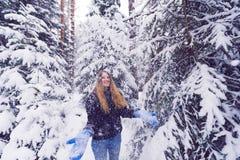 Härlig stående av en flicka i vinterskog som ler kvinnan som spelar i snö Royaltyfria Foton