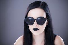Härlig stående för kvinnamodemodell i solglasögon med svarta kanter och örhängen Idérik frisyr och smink Fotografering för Bildbyråer