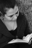 Härlig stående för ung kvinna som läser en bok under ett träd Arkivbild