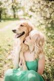 Härlig ståendekvinna med gulligt sitta för golden retrieverhund arkivfoton