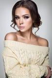 härlig ståendekvinna Ung dam som poserar i varm tröja Trevlig makeup och frisyr Arkivbild