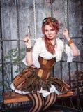Härlig steampunkkvinna i buren med vapnet Royaltyfri Fotografi