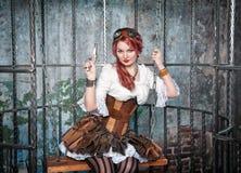 Härlig steampunkkvinna i buren med vapnet Arkivbild