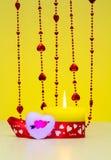 Härlig stearinljus för bränning för St-valentindag bredvid en hjärta och pärlor Arkivfoto