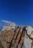 Härlig sten under den blåa himlen på stranden Arkivbild