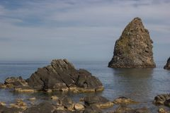 Härlig stenig kustlinje för Aci Trezza och cyclopean öar i en blå himmel royaltyfri bild