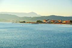 Härlig stenig kustlinje, i att förbluffa det blåa Ionian havet på soluppgång i den Sidari stugby på den Korfu ön med berömd kanal arkivbild