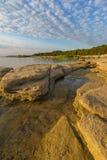Härlig stenig seacoast i morgonsolljuset royaltyfria bilder