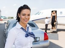 Härlig stewardess Standing Against Limousine Arkivfoton