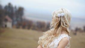 Härlig stilfull blond brud med blåsigt långt hår som poserar på den suddiga slottbakgrunden stock video