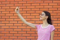 Härlig stilfull flickadanandeselfie på bakgrund för tegelstenvägg royaltyfri foto