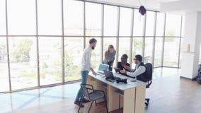 Härlig stilfull personal som sitter i kontoret på skrivbordet genom att använda en bärbar dator och lyssna till en kollega arkivfilmer